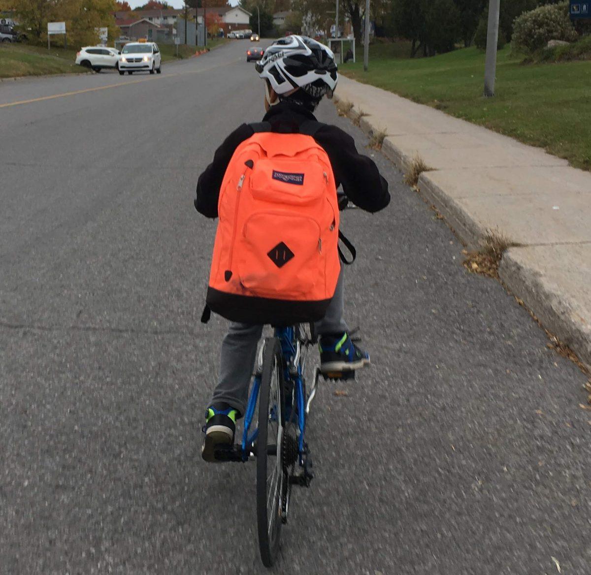 Un enfant à vélo sur la route de l'école